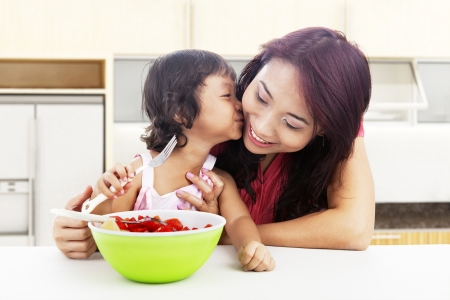 Cute asian little girl with fruit salad kissing her mother  shot in the kitchen photo