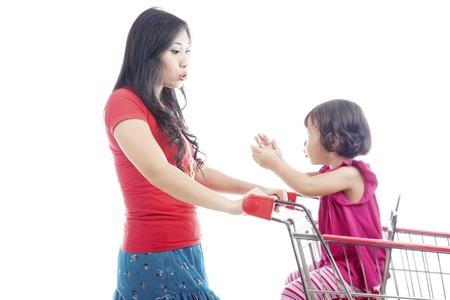 ni�os de compras: Retrato de la madre joven asi�tico empujando un carrito de compras y hablando con su hija en el carrito de compras.