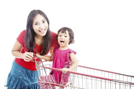 Portret van glimlachende moeder met haar dochter in de winkelwagen