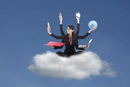 Beautiful asian business woman looking confident with six arms sitting on a cloud photo