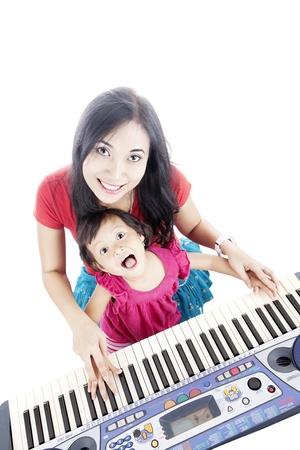 Porträt der jungen asiatischen Mutter und ihre Tochter spielt Klavier. isoliert auf weiß