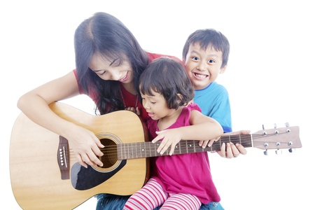 Portrait of female musician plays guitar with her children. shot in studio isolated on white photo