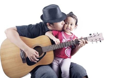 femme avec guitare: Plan d'un musicien embrasser son tir fille en studio sur fond blanc