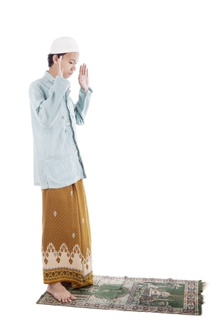 Portrait of muslim man praying on mat. shot in studio isolated on white photo