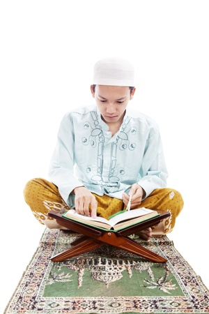 Portrait of man reading quran and pointing at the quran. shot in studio isolated on white photo