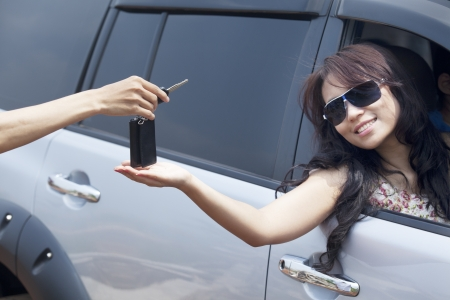 selling service smile: Cropped view of a hand giving a car key to beautiful asian woman Stock Photo
