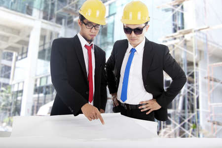 Two Asian engineer discussing the blueprint at construction site, shot outdoor photo