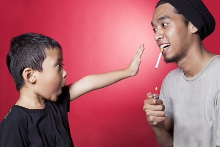 man smoking: Cute asian boy asking a smoker to stop smoking. shot in studio over red background Stock Photo