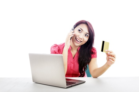 An attractive woman purchasing product online using her laptop computer, credit card, and mobile phone photo