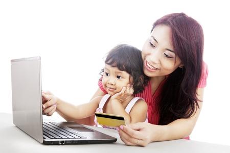 ni�os de compras: Mujer asi�tica joven que da a la educaci�n de compras en l�nea para su hija