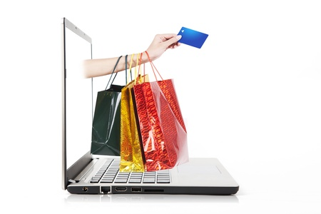 mobile shopping: Hand holding credit card and shopping bag from laptop computer
