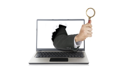 Businessman hand holding mgnifying out from laptop computer photo