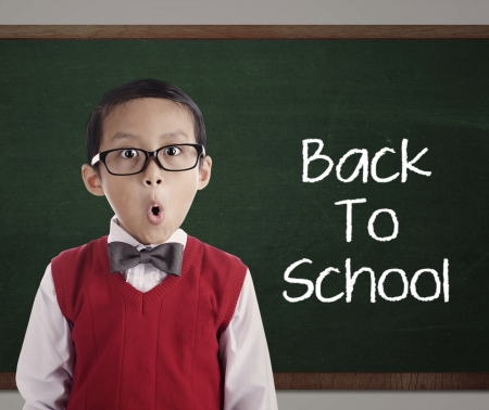 word of mouth: Portrait of little asian elementary school pupil with text of Back To School on the blackboard