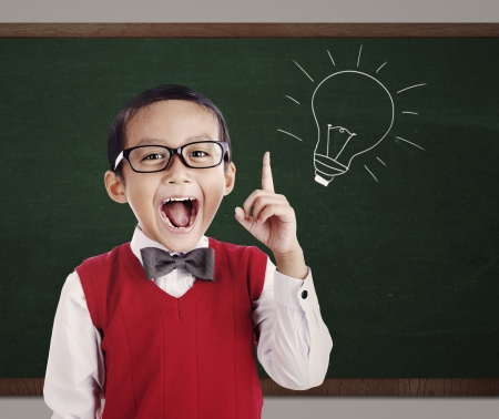 Portrait of male elementary school student with lightbulb picture on blackboard photo