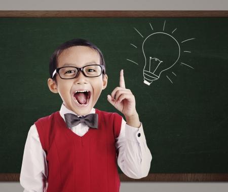 Portret van mannelijke basisschool student met gloeilamp beeld op blackboard Stockfoto