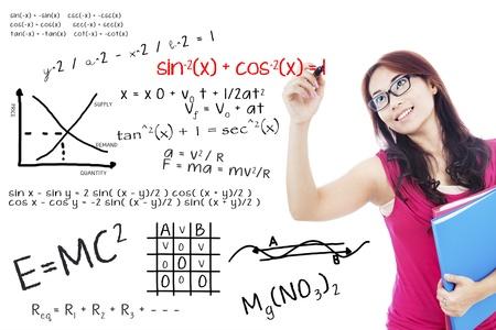 simbolos matematicos: Retrato de estudiante universitaria con marcador para escribir la f�rmula matem�tica en la pizarra