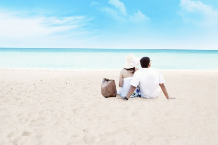 young asian girl: Young couple sitting together on beach. shot at tropical beach Stock Photo