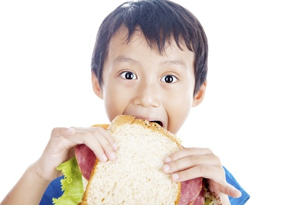 sandwich bread: Asian little boy eating big sandwich. shot in studio isolated on white