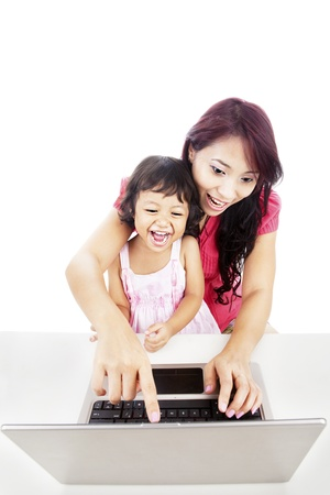 Portrait of mother and her daughter using laptop computer by pointing on the monitor photo