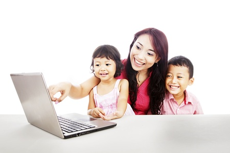 Happy young mother with her children using ultrabook laptop computer to enjoy entertainment  photo