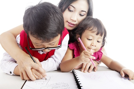 guiding: Young asian mother guiding her children to learn how to write