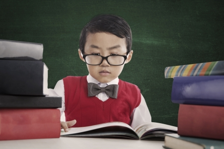 Portrait of nerd pupil reads book seriously in front of blackboard photo