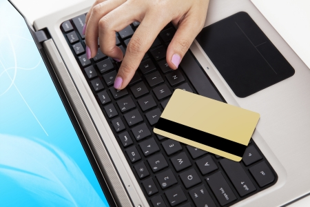 non cash: Close up of laptop computer with a credit card and a hand - payment concept