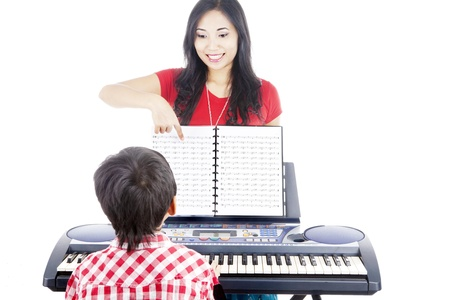 teaching music: Young boy taking piano lessons at home with his tutor Stock Photo