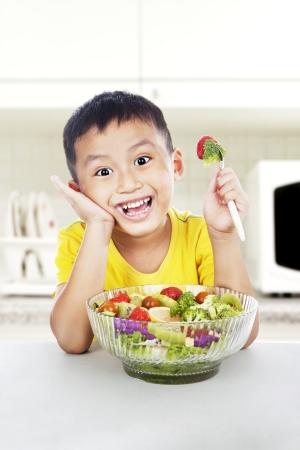 Giovane bambino asiatico con insalata sorridente in cucina. girato in cucina Archivio Fotografico