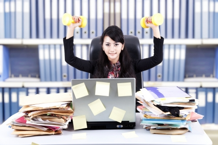Powerful businesswoman exercising with dumbbells at office photo