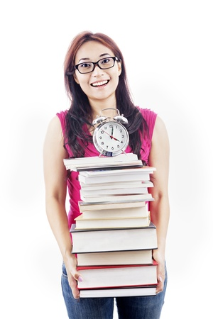 Exams time concept: college student prepares a pile of textbooks and alarm clock for preparing exams Stock Photo