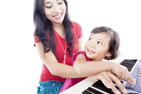 music education: Portrait of young asian mother with her daughter pressing a button on the piano Stock Photo