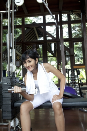 Beautiful asian woman lifting dumbbell in gym photo