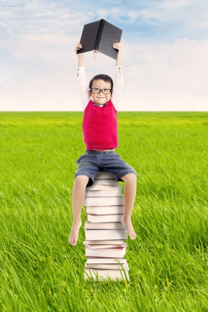 Portrait of little pupil holding a book and sitting on a stack of books. shot on the meadow