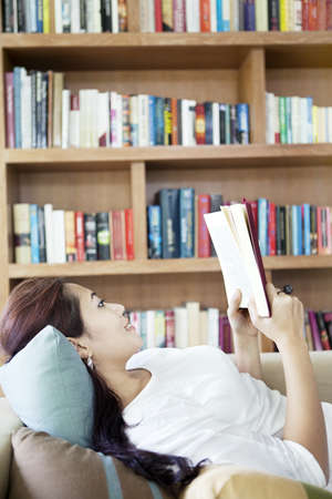 Charming woman reading a book lying on a sofa in a living room with bookshelf background photo