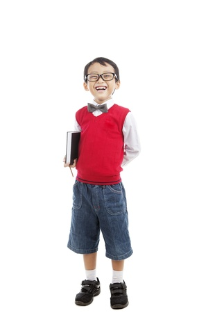 Back to school concept: Smiling elementary school boy holding book and ready for school photo