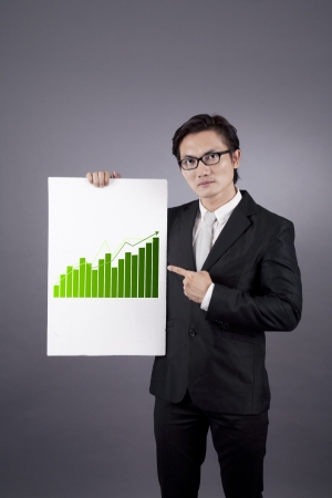 Young asian businessman presenting a report of growing business by pointing at the business chart photo