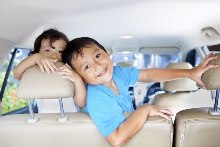 Asian children ready for a road trip posing in car photo