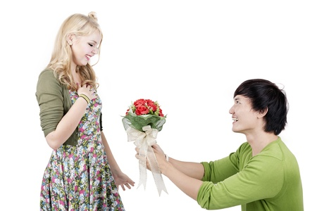 Young asian man on knees giving woman bouquet of flowers.