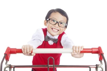niño empujando: Retrato de feliz estudiante de primaria empujando carro de la compra