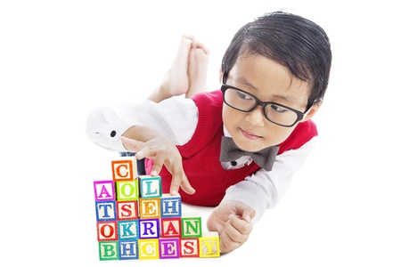Portrait of male elementary school student playing alphabet blocks with finger stepping upward on the stairs of blocks photo