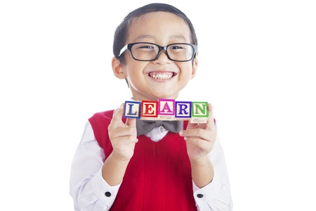 Portrait of asian elementary school student showing LEARN word. shot in studio isolated on white