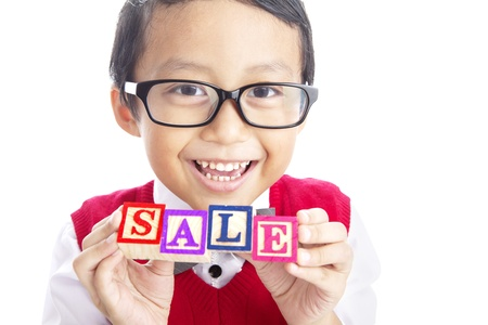 Portrait of asian elementary school student showing SALE word. shot in studio isolated on white photo