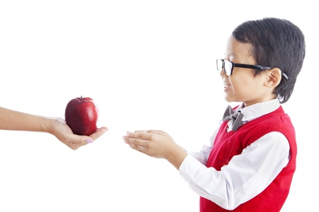 Portrait of asian schoolchild receiving a red apple from his teacher. shot in studio isolated on white photo