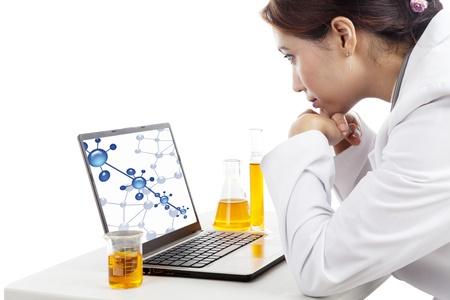 investigador cientifico: Joven cient�fico hembra mirando una reacci�n mol�cula en la pantalla del ordenador port�til