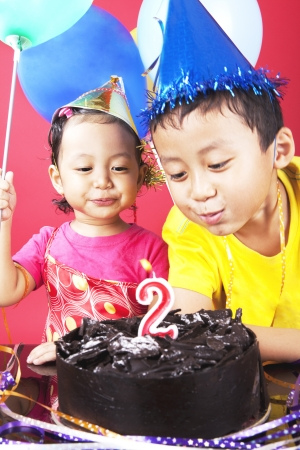 Asian sibling celebrating second birthday, shot in studio at birthday party photo