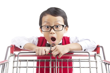 niño empujando: Expresión de asombro estudiante de escuela primaria mirando cesta de la compra