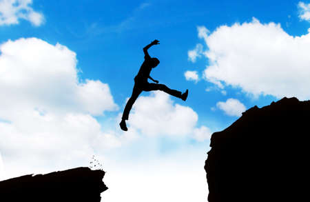 Silhouette of young asian man jumping over cliff photo