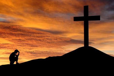 hombre orando: Un paisaje espectacular cielo con una cruz de montaña y una persona meditando pensando. Un símbolo de fuertes luchas internas.