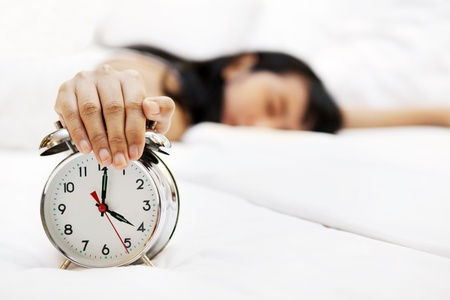 snooze: Lazy woman sleeping with hand covering an alarm clock in front Stock Photo